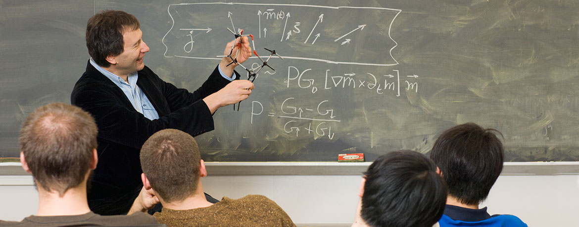 professor in front of a chalkboard explaining a theory to students
