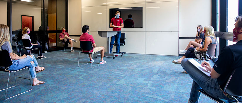 group of students in a meeting room physically distanced with 6 feet apart