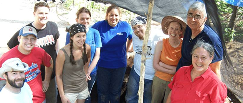 Graduate students posing at a dig site.