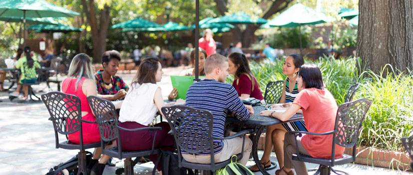 Eight students sitting around a table on the Russell House patio, an umbrella shading them from the sun