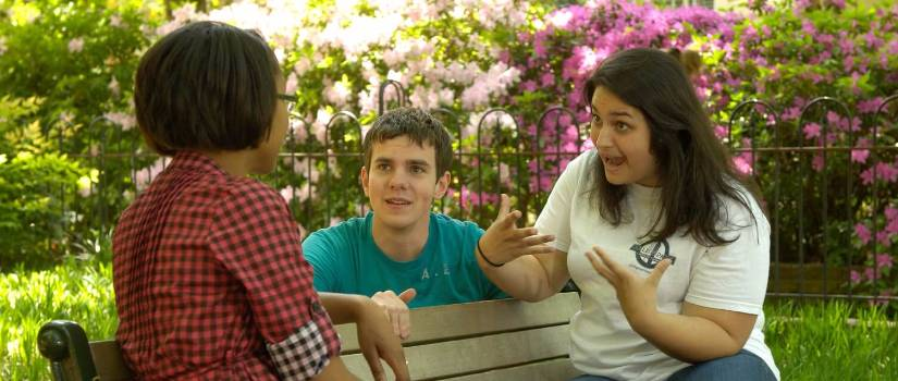 Students talking on a bench.
