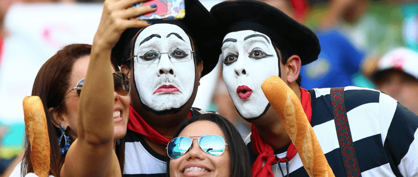 Student holding baguette and taking a selfie with a sad mime.