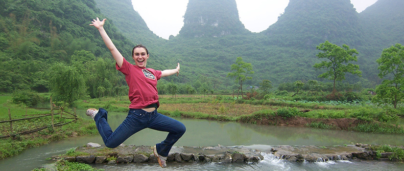 Student leaping triumphantly in the mountains.