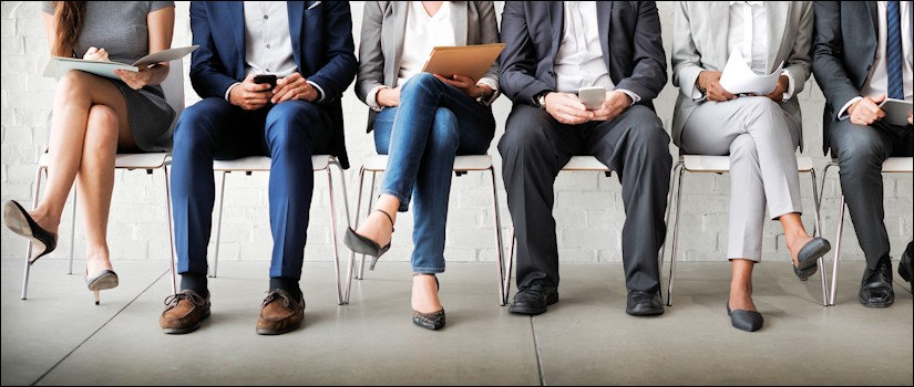 Waist-down view of sitting job applicants in waiting room