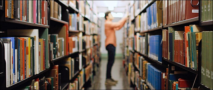 Student searching for book among shelves in library