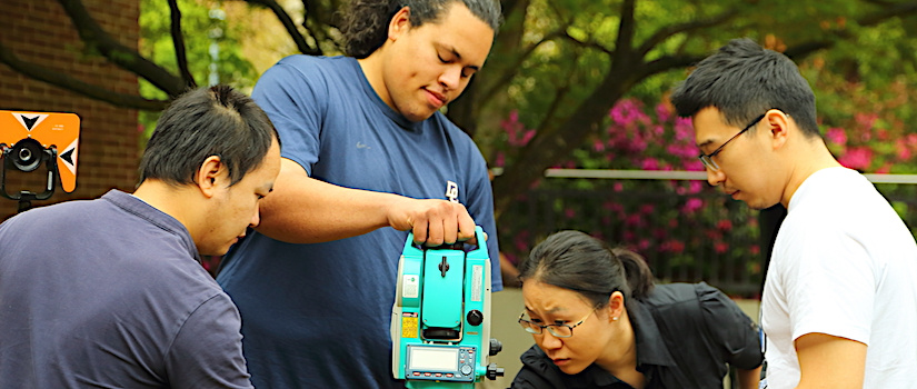 Grad students setting up a surveying project with the Total Station