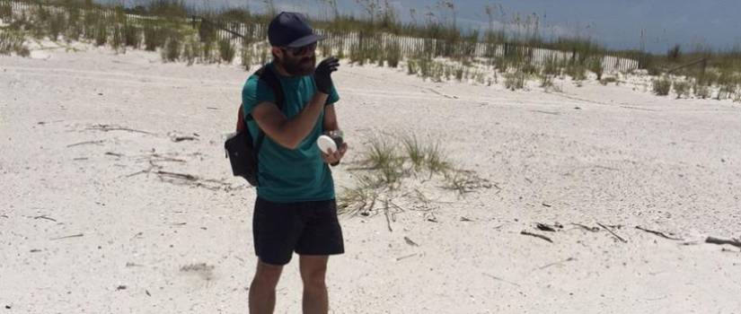 Joel Bostic collects samples from a beach on the Gulf of Mexico.
