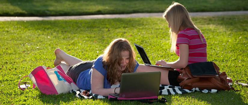 Two girls with laptops lounging on grass in the sun