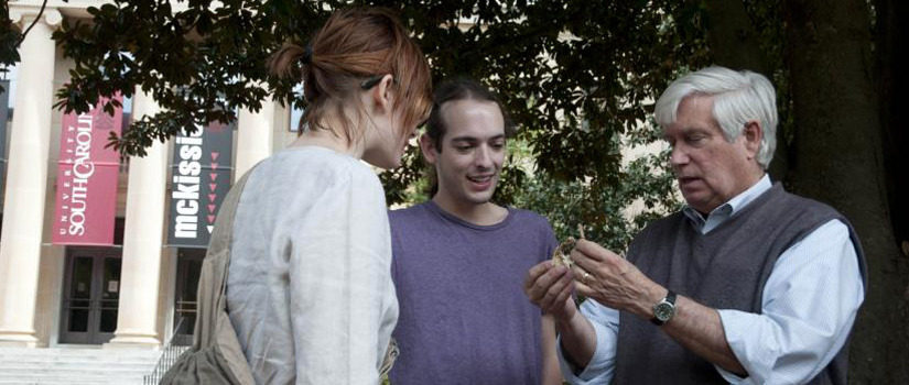 Man explaining an artifact to two students outside the museum