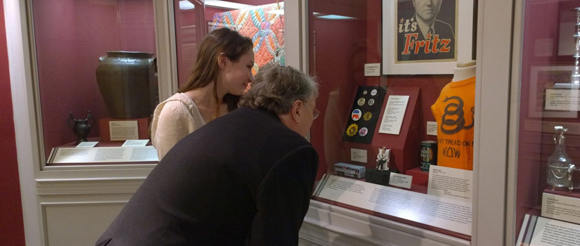 Group examining artifacts in a glass case.