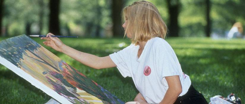 student painting in the grass