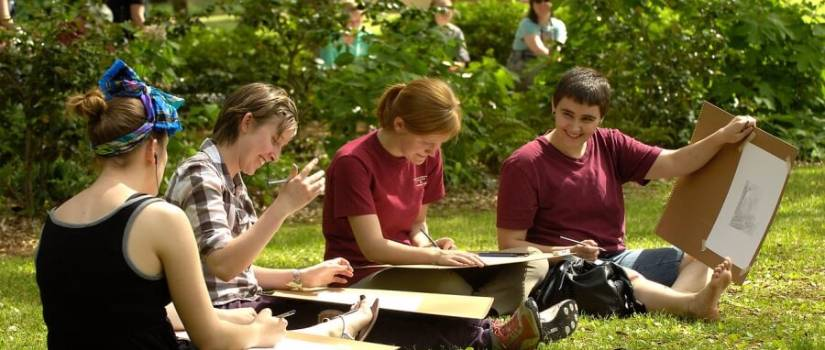 A group of students sit on the grass and draw.
