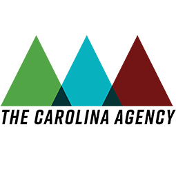 Formal logo - three slightly overlapping triangles, side by side, in the following order from left to right; Green, Blue and Red. Where the triangles overlap it is colored Black. Beneath the triangles is written The Carolina Agency.