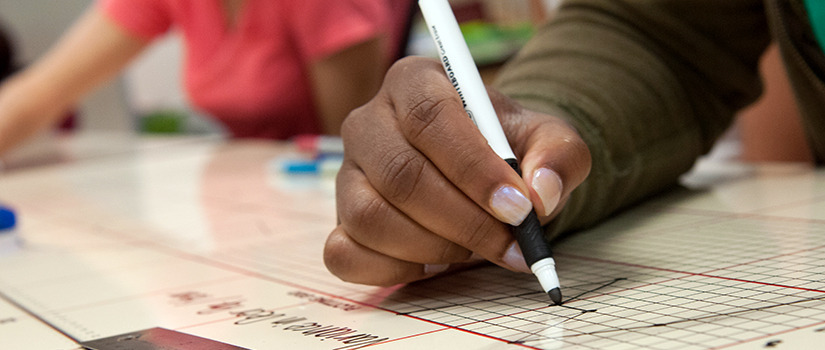 A brown-skinned hand with lacquered nails writes with a dry erase marker on a chart while other people work in the background.