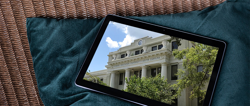 A handheld tablet lying on a pillow shows Wardlaw College