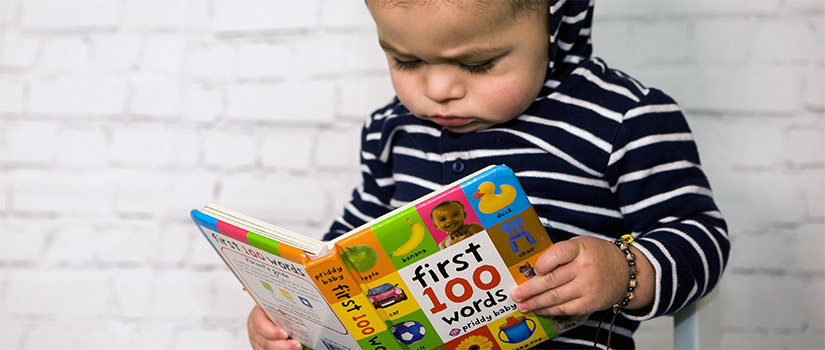 "a toddler reading a book titled ""first 100 words"""
