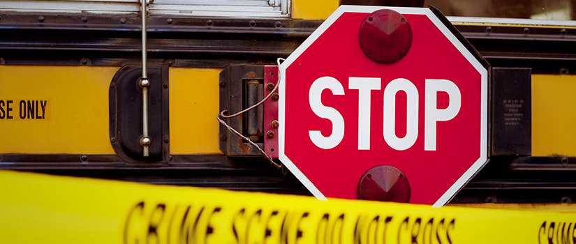 The side of a school bus with cordon tape that reads CRIME SCENE DO NOT CROSS