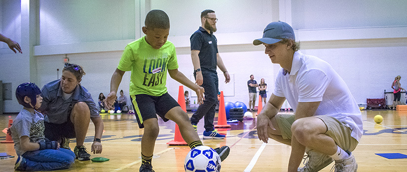 An adapted physical education teacher leads a student in a physical activity involving a soccer ball