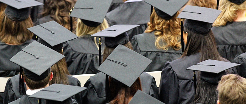 several people in black graduation caps and gowns, seen from behind.