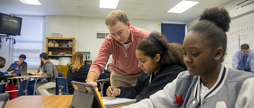 A teacher points to a tablet that a student is working on while another student smiles in the foreground.