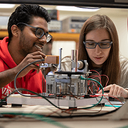 a male and female student work together in an electrical engineerin lab