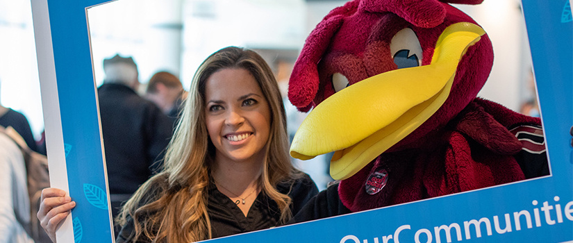 woman poses with Cocky at the E-Week Open House