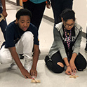 two students test experiment in the hallway