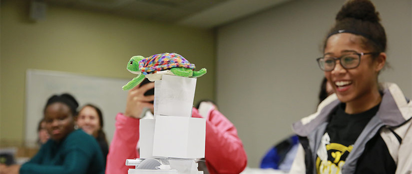 date night participant smiles at paper tower with stuffed turtle on top