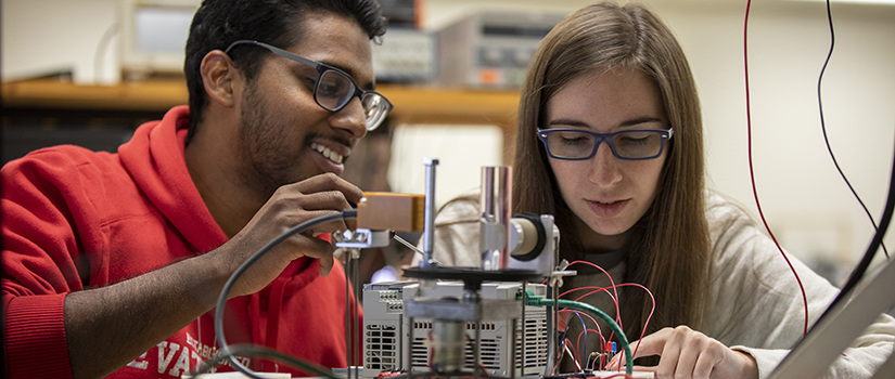 a male student and a female student work on an electrical device together during class