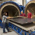 a student and two faculty members inspect material ready for the composite machine