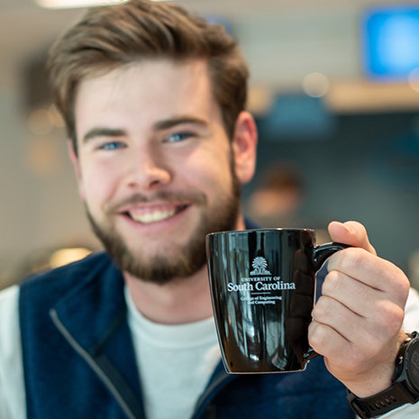 student holds black coffee mug with college logo on it