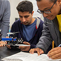 two students work on a drone