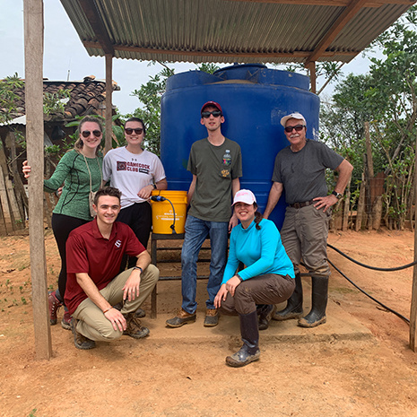 CEC students stand around a water cooler in Ecuador