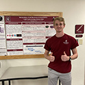 Jonathan Gray stands with his research poster