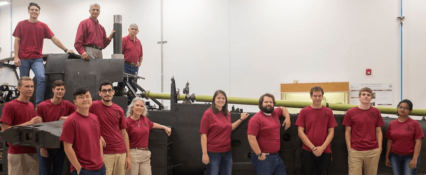 research team poses in front of apache helicopter in Mcnair Center