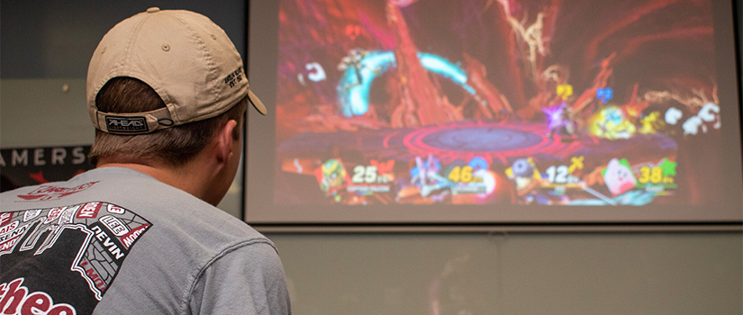 a student plays super smash brothers on the projector
