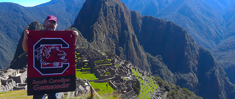 Director Rich Harrill holds a UofSC banner while visiting Machu Picchu