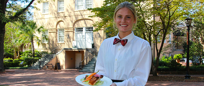 A female hospitality management student stands on the Horseshoe in front of the historic McCutchen House. She holds a delicious-looking plated meal.