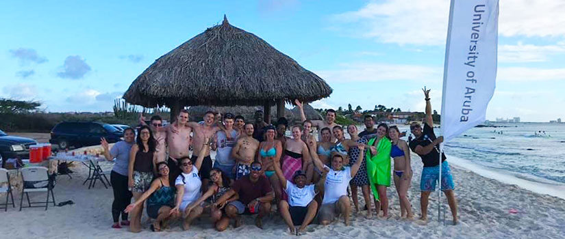 Students pose on the beach during orientation week at the University of Aruba