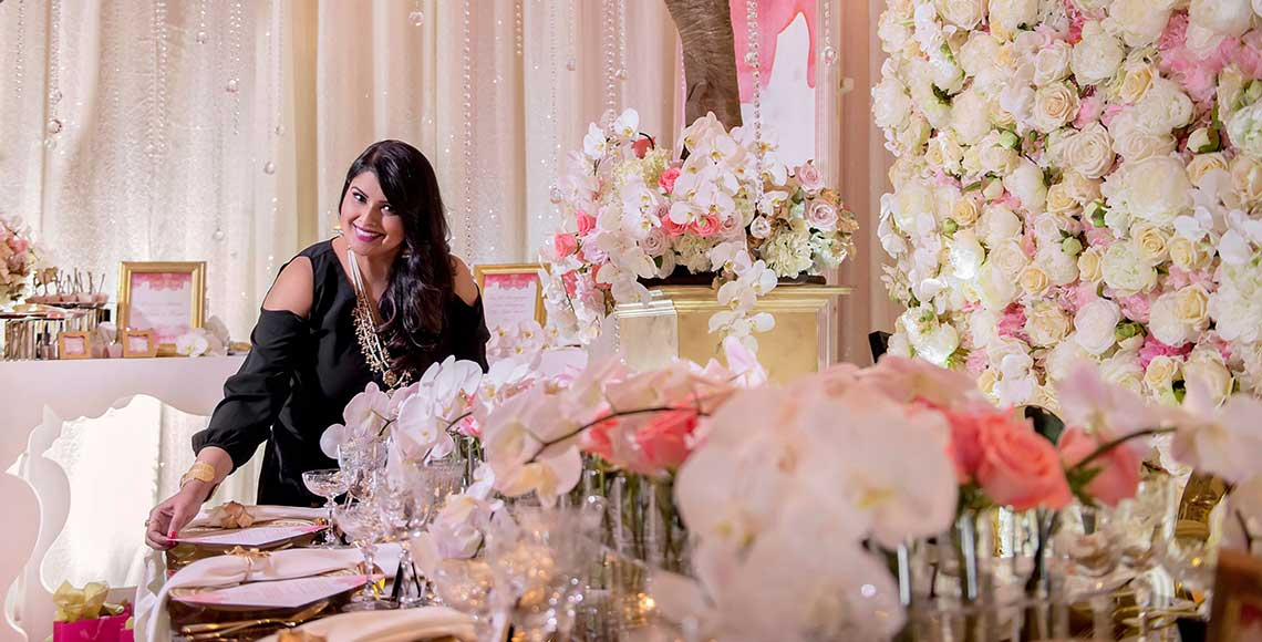 Nirjary Desai, a hospitality management alumnus, stands in a wedding banquet room surrounded by roses, decorated trees and branches, and a sumptuous dining table