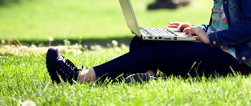 Close-up of a student using a laptop while sitting on a green lawn.