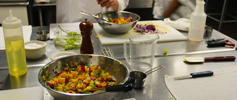 A colorful mixture of mango salsa is displayed on top of a cooking table in the culinary kitchen at McCutchen House.