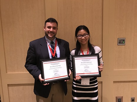 David Cardenas stands with Graduate Student Rui Qi as they receive their certificates of achievement in research at HRSM's faculty, staff and student awards day.
