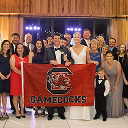 Lori Anna Varnadoe and Lee Davis with their wedding party. The bride and groom hold a Gamecock banner.