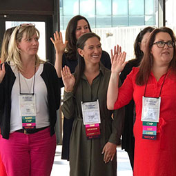 Christina Saragnese raises her right hand with a group of inductees at the Society of Government Meeting Professionals National Chapter Board meeting.