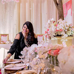 Nirjary Desai stands in a room decorated for a bridal reception with lush flowers and formal table setting