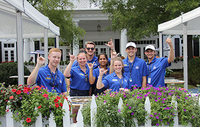 "HRTM students working the PGA tournament at Charlotte's Quail Hollow Club pose signalling the ""spurs up!"" hand sign while standing in front of the clubhouse."