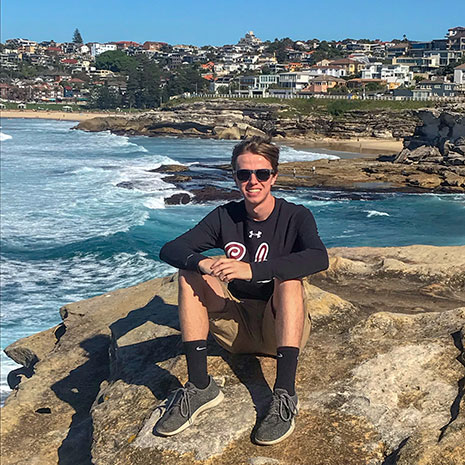 David Brake takes a moment to pose on a beach in Austria. Brake, who spent more than three months at Deakin University in Australia, researched environmentally sustainable practices of major sporting venues in Australia and compared them to venue management practices in the United States.