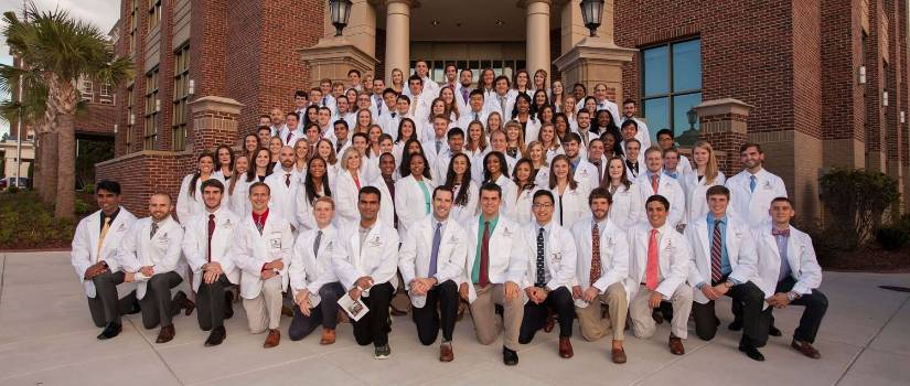 Students posing in white coats.