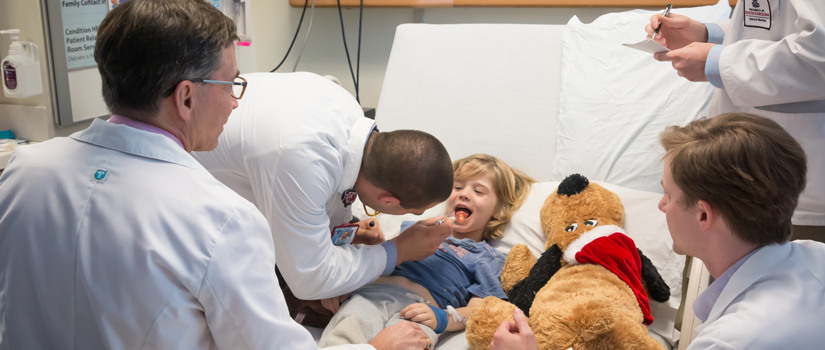 Doctors using a light to examine a young child's throat.
